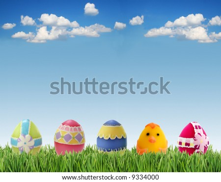 Easter eggs in grass on sky background - stock photo