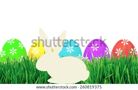 Easter eggs in green grass and paper rabbit isolated on white