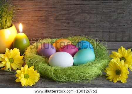 Easter eggs in green nest on vintage wooden planks