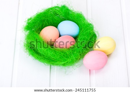 Easter eggs in green nest on white board - stock photo