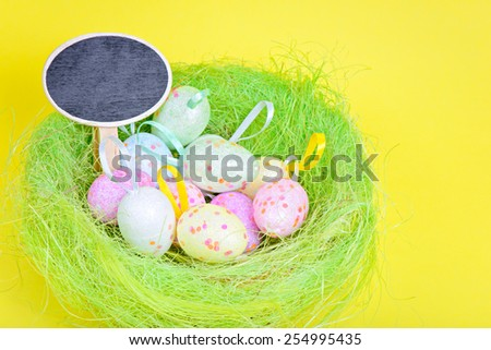 Easter eggs in green nest with copy-space board over yellow paper - stock photo