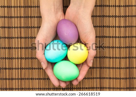 Easter eggs in hands over wooden mat - stock photo