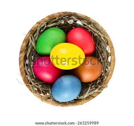 Easter eggs in nest basket isolated on white background. Top view - stock photo