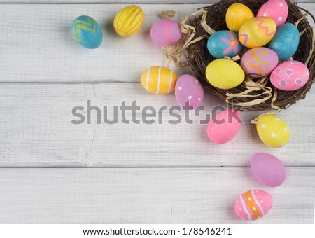 Easter Eggs in Nest from Top View Looking Down on White or Gray Rustic Wood Background with room or space for copy, text, words - stock photo