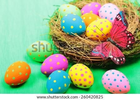 Easter eggs in nest on green background - stock photo