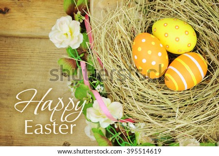 Easter eggs in nest on rustic wooden planks