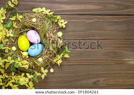 Easter eggs in nest on rustic wooden planks with flowers - stock photo