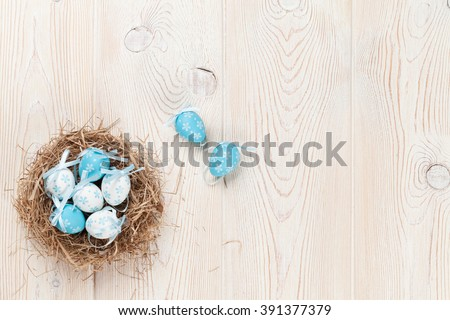 Easter eggs in nest over wooden background. View with copy space - stock photo
