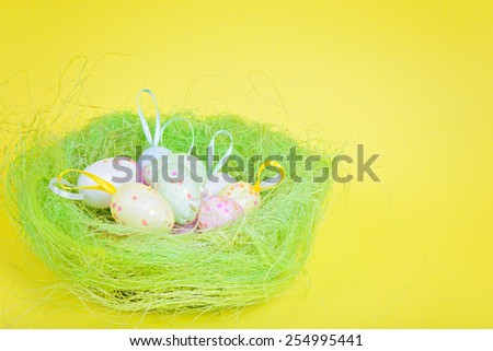 Easter eggs in nest over yellow paper - stock photo