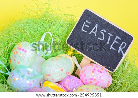 Easter eggs in nest with copy-space chalkboard over yellow paper - stock photo