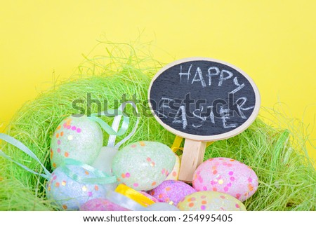 Easter eggs in nest with small blackboard over yellow paper - stock photo