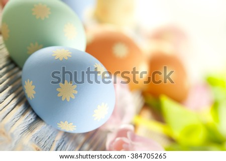Easter eggs in pastel colors and spring flowers - stock photo