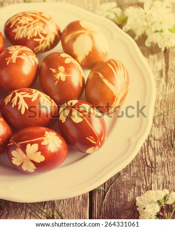 Easter Eggs in Plate on Wooden Table Decorated with Natural Fresh Leaves and Boiled in Onions Peels. Toned - stock photo