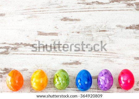 Easter eggs in rainbow colors on rustic bright wooden background - stock photo