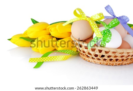 Easter eggs in the basket and yellow tulips isolated on a white background - stock photo