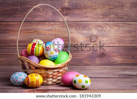 Easter eggs in the basket of wooden boards - stock photo