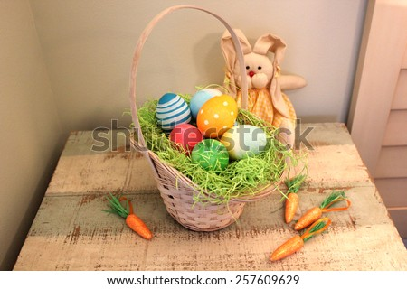 Easter eggs in the basket on the wooden background. - stock photo