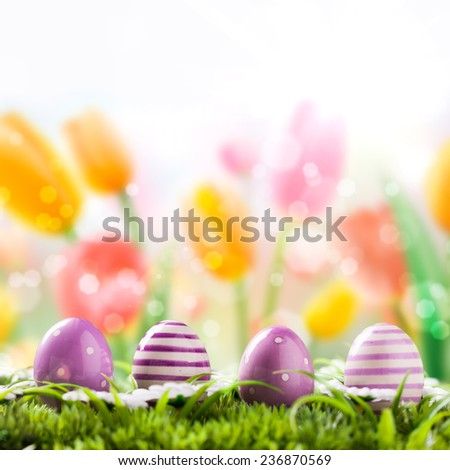 easter eggs in the grass in front of many tulips - stock photo