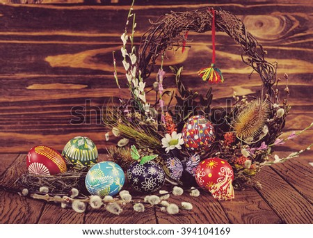 Easter eggs in the nest, decorative butterfly, flowers and blooming willow on the wooden background. Easter decoration. Happy Easter Instagram toning effect - stock photo