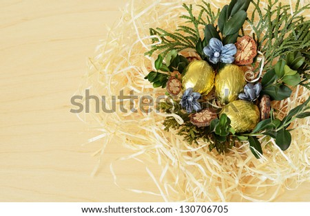 Easter eggs in the nest on a wooden background - stock photo