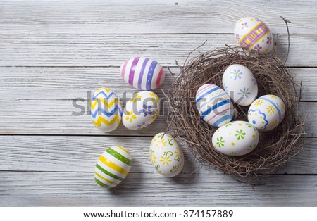 Easter eggs in the nest on rustic wooden background - stock photo