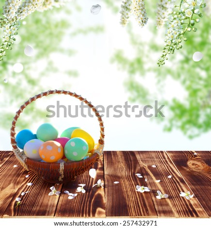 Easter eggs in the nest on rustic wooden table - stock photo