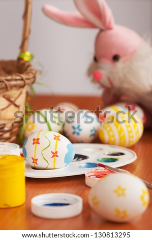 Easter eggs in the process of drawing with a rabbit in the background - stock photo