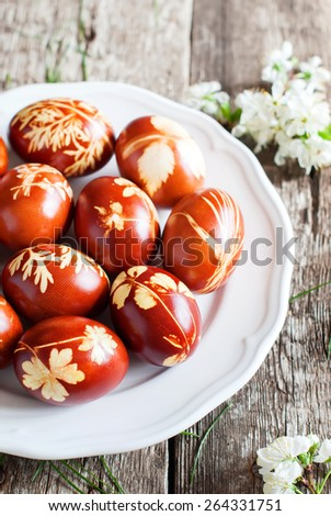Easter Eggs in white Plate on Wooden Table, Decorated with Natural Fresh Leaves and Boiled in Onions Peels - stock photo