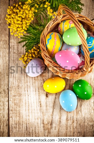 Easter eggs in wicker basket and branch mimosa on wooden board with above copyspace - stock photo