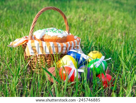 Easter eggs in wicker basket with napkin and Easter cake on green grass