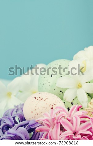 Easter eggs lying in a bed of spring flowers against a blue background with room for copy space. Selective focus with extreme shallow DOF. - stock photo