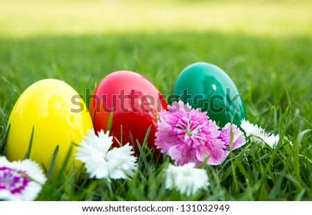 Easter eggs on green grass with flower
