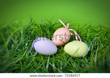 Easter eggs on the grass with green background with copy space - stock photo