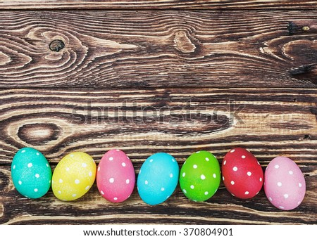 Easter eggs on wooden background. Focus on the wooden table - stock photo