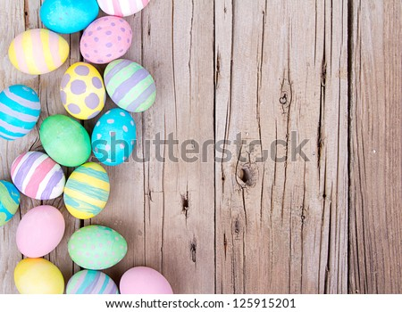 Easter eggs painted in pastel colors on a wooden background - stock photo