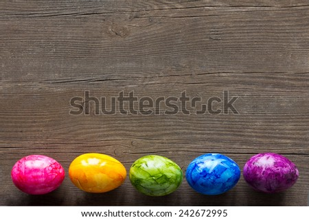 Easter Eggs painted in various colours on dark wood,  copyspace - stock photo