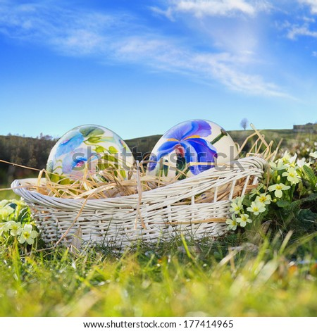 Easter eggs painted with flowers in a basket . Blue sky in background - stock photo