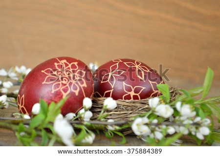 Easter eggs painted with wax and spring flowers  - stock photo