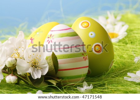 Easter Eggs sitting on grass field with blue sky - stock photo