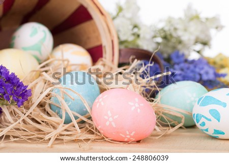Easter eggs spilled from a basket onto a wood surface - stock photo