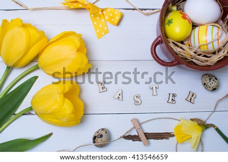 Easter eggs, tulips and other decorations over white wooden table. Top view.