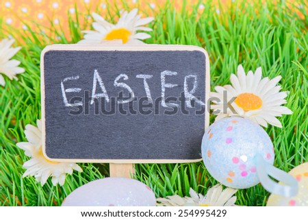 Easter eggs with blackboard on the grass with copy-space - stock photo
