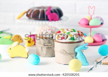 Easter eggs with cake on a white wooden table - stock photo
