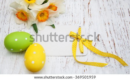 Easter eggs with daffodil flowers and greeting card