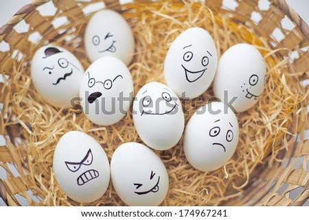 Easter eggs with different facial expressions in basket - stock photo