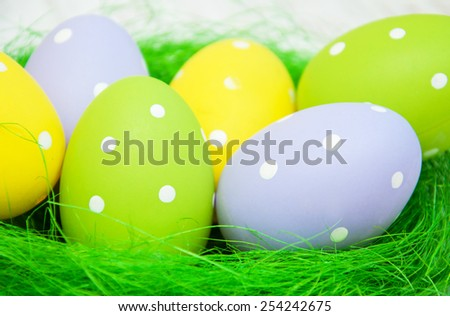 Easter eggs with flowers on a green nest - stock photo