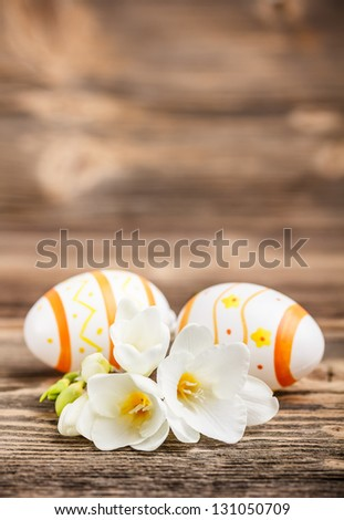 Easter eggs with freesia flower on wooden plank - stock photo