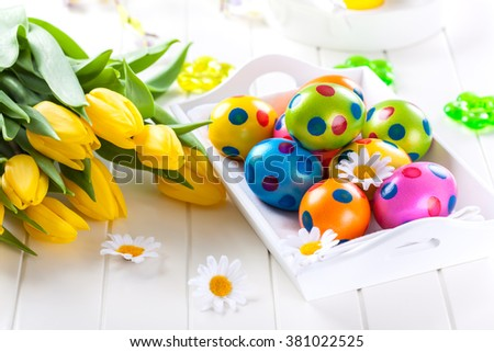 Easter eggs with fresh tulips  - stock photo