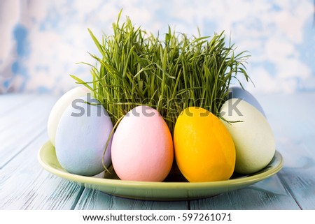 Easter Eggs With Grass Served On The Plate On A Blue Background
