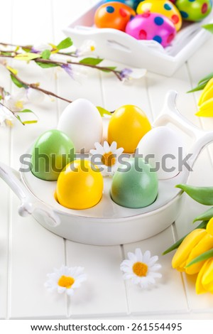 Easter eggs with spring flowers decorating table - stock photo